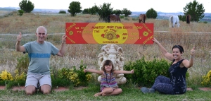 Richard and Vidya hold the painted version of the mantra in the garden at Suryalila, Spain